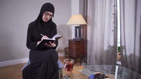 Thumbnail for Concentrated Muslim Woman in Eyeglasses Writing at Home. Successful Modern Female Writer in Hijab