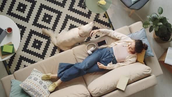 Woman Lying on Sofa and Petting Dog