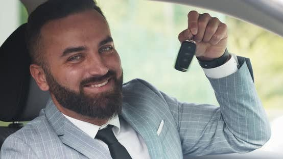 Confident Businessman Smiling To Camera and Showing Key of His New Car, Close Up