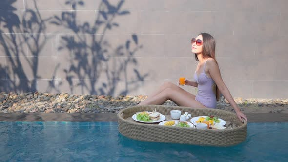 Woman with floating breakfast in pool