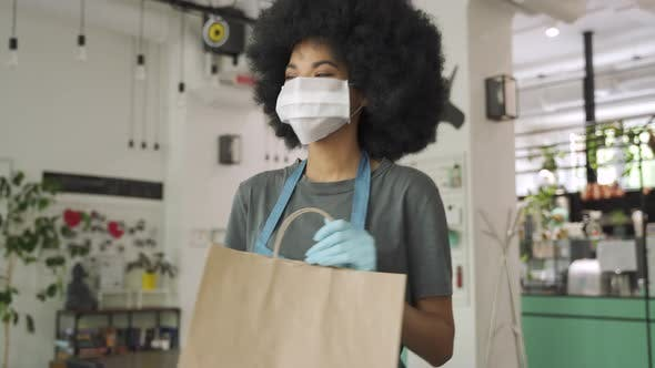 African Female Cafe Worker Wear Face Mask Giving Takeaway Food Bag To Customer