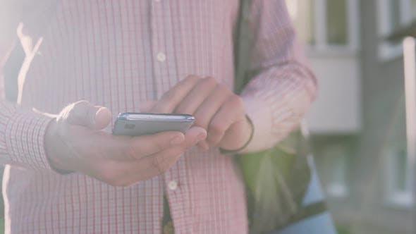 Thumbnail for Ein Mann geht die Straße hinunter und tippt eine Nachricht am Telefon gegen den Sonnenuntergang
