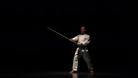 Thumbnail for Kendo Fighter on White Kimono Practicing Martial Art with the Bamboo Bokken on Black Background.
