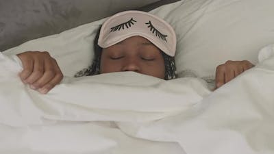 African American Woman in Sleep Mask in Bed