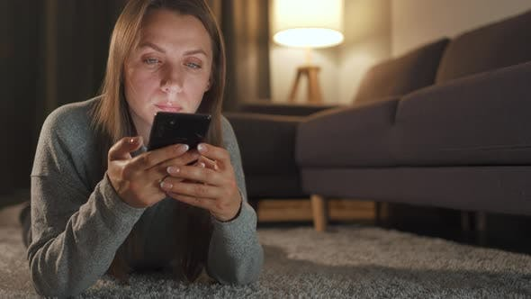 Thumbnail for Woman Is Lying on the Floor and Using Smartphone in the Evening