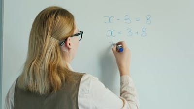 Rear View: The Teacher Solves the Equation in Algebra. Online Lessons for Elementary School