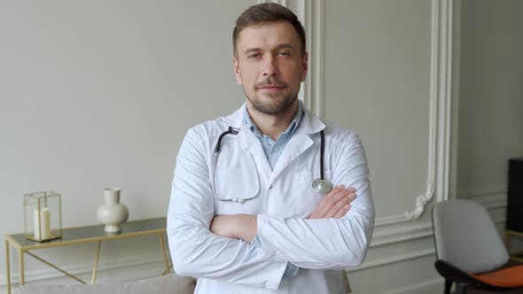 Portrait of a Doctor with Stubble in a White Lab Coat and a Stethoscope Around His Neck Arms Crossed