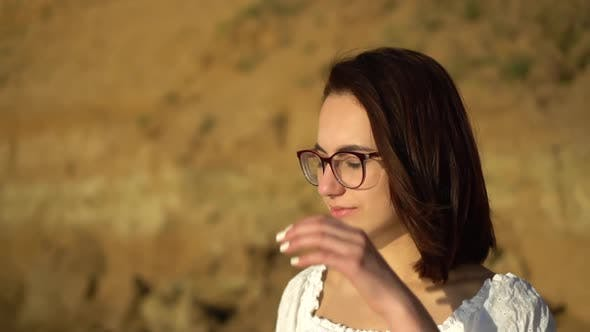 Cover Image for Attractive Young Woman on the Background of a Clay Rock. A Girl with Glasses Straightens Her Hair