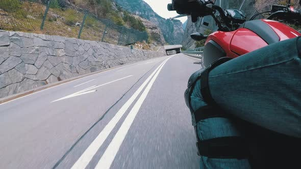 Motorcyclist Rides Along on the Scenic Mountain Curve Road. Side View. POV.