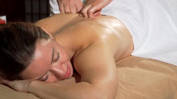 Thumbnail for Attractive Woman Smiling with Eyes Closed, Enjoying Soothing Back Massage