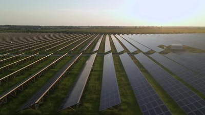 Aerial Drone View Into Large Solar Panels at a Solar Farm at Summer Sunset
