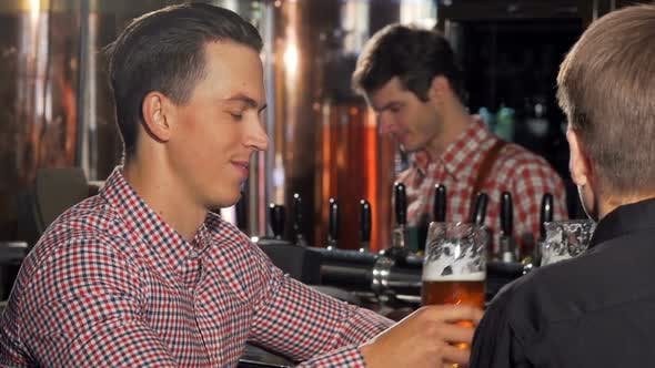 Thumbnail for Handsome Happy Man Enjoying Delicious Beer, Talking To His Friend at the Pub