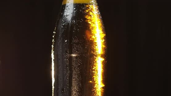 Thumbnail for Bottle of Cold Beer on a Black Background. It Slowly Rotates. Condensate