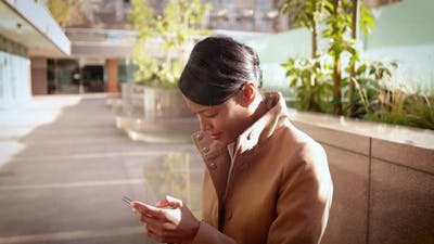 Mixed ethnicity business woman works on her cellphone