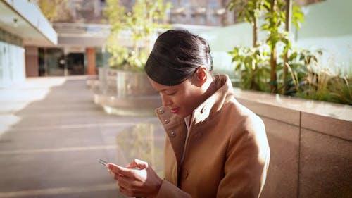 Geschäftsfrau mit gemischter ethnischer Zugehörigkeit arbeitet an ihrem Handy