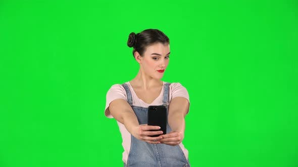 Thumbnail for Girl Makes Selfie on Mobile Phone Then Looking Photos on Green Screen