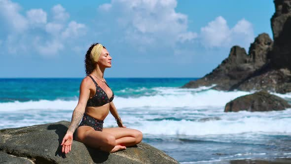 Cover Image for Yoga Practice at Sunset. Yong Woman Sits in Lotus Pose on the Stone and Meditates on the Beautiful