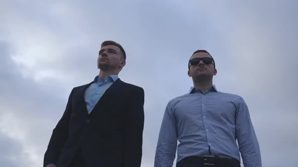 Thumbnail for Two Young Businessmen Walking in the City with Blue Sky at Background. Handsome Coworkers Commuting