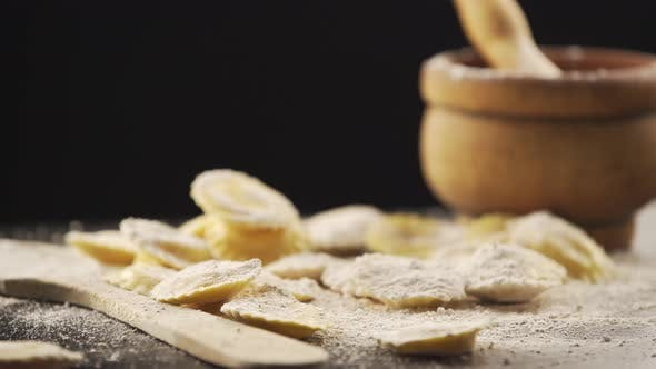 Leckere rohe Ravioli mit Mehl und Basilikum auf Holztisch rotierenden
