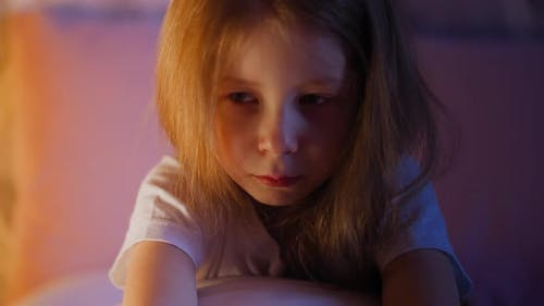 Depressed Little Girl Embraces Pillow Sitting Alone on Bed