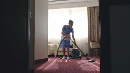 Housemaid Vacuuming Hotel Room