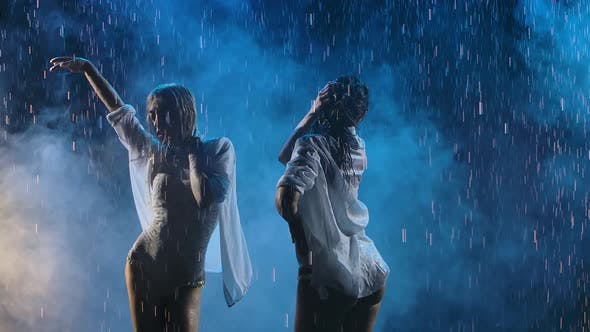Thumbnail for A Blonde and a Brunette in Wet White Shirts Are Dancing Passionately in the Rain. Silhouettes of Wet