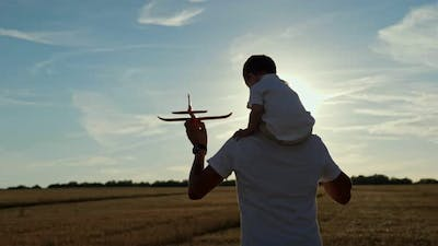 Man Carries Toddler Son on Shoulders and Toy Plane in Hand