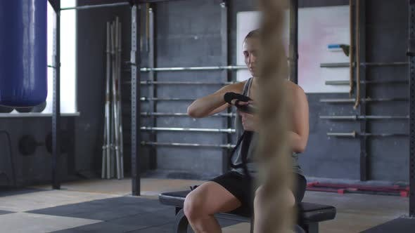 Thumbnail for Young Sportswoman Unwrapping Hands in Gym