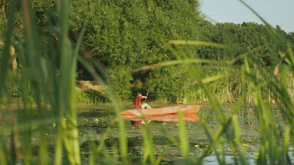 Thumbnail for Fitness woman is rafting along river in red kayak.