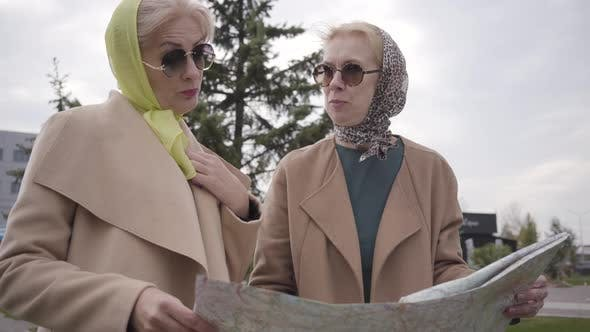 Thumbnail for Close-up of Two Mature Women in Headscarves and Sunglasses Holding the Map and Talking