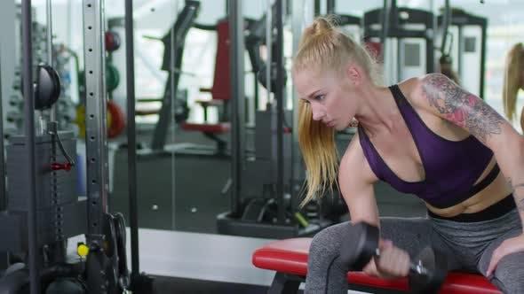 Frau Performing Hantel Curl im Fitnessstudio