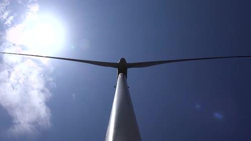Upward View of a Wind Turbine With Sky Background