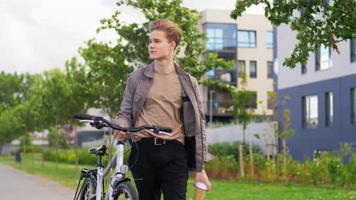 Young Man with Bicycle and Coffee Walking in City