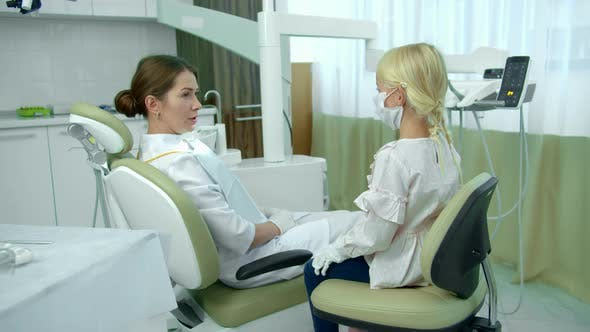 Thumbnail for Dentist Sits in Patient Chair and Talks with Girl