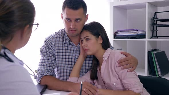 Problems with Health, Desperate Frustrated Family Couple Talking with Doctor About Fertility and