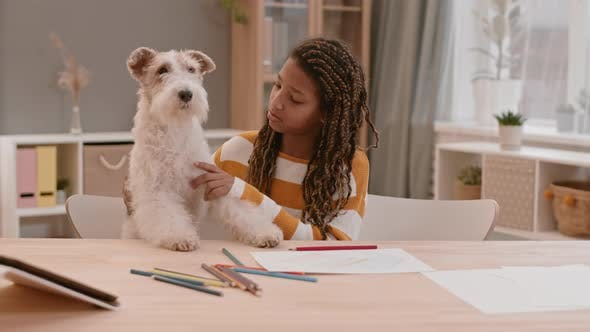 Girl and Dog Sitting by Desk