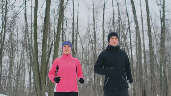 Thumbnail for A Man and a Woman in a Pink Jacket in the Winter Running Through the Park in Slow Motion. Healthy