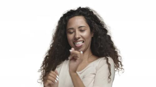 Closeup of Happy Latino Girl with Long Curly Hairstyle Wearing Casual Tshirt Dancing and Smiling