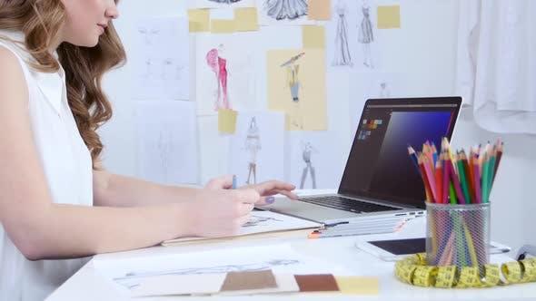 Cover Image for Designer schaut sich den Computer an und wählt Farbtöne für eine neue KleidungsSammlung aus