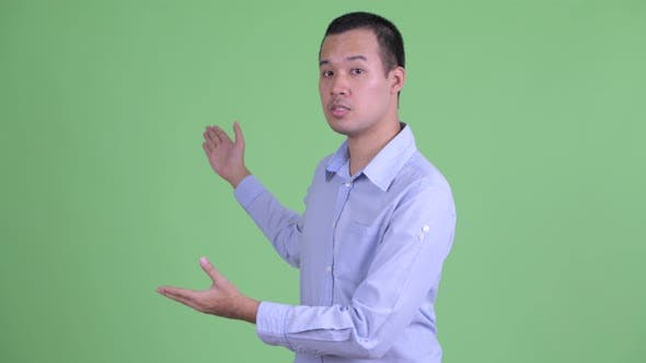 Thumbnail for Studio Shot of Happy Asian Businessman Presenting Something