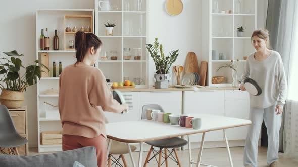 Zwei junge Frauen spielen Ping Pong mit Geschirr zu Hause