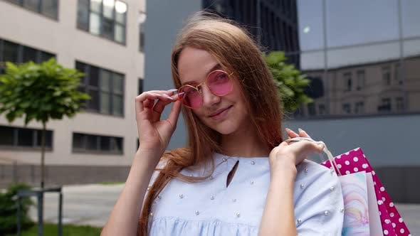 Thumbnail for Young Woman in Pink Sunglasses Standing in Front of the Shopping Mall and Holding Shopping Bags