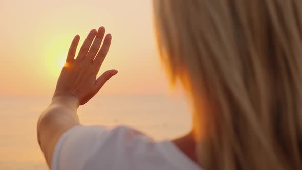 Cover Image for The Woman Extends Her Hand To the Sun Rising Above the Sea. Enjoy the Warmth and Fly of the Concept