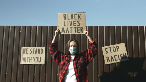 """Thumbnail for Caucasian woman holds poster """"Black lives matter"""" above head against brown background wearing mask"""