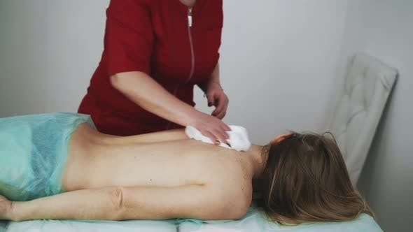 Therapist Cleans Woman Back with Towel After Procedure