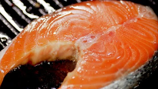Fresh Salmon Steak Is Fried with Spices in a Frying Pan.
