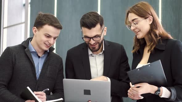 Three Coworkers Working on a Project at Office