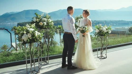 Romantic wedding couple looking to each other and smiling holding hands with flowers