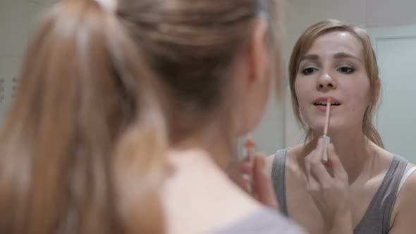 Thumbnail for Young Woman Putting Lipstick on Lips, Mirror