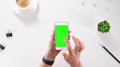 Woman using mobile phone, interacts, touches the screen and points to the screen with her finger.